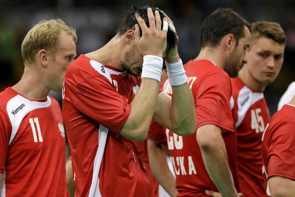 Krzysztof Lijewski trzyma się za głowę i wpatruje w podłogę