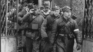 """Romuald Rajs """"Bury"""", dowódca 1. kompanii (szturmowej) 3. Wileńskiej Brygady AK, i jego żołnierze opuszczają kościół po mszy rezurekcyjnej. 9.04.1944, Turgiele"""