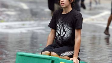 Młody mieszkaniec dzielnicy Soho na Manhattanie pływa po zalanej ulicy na skrzynce na gazety