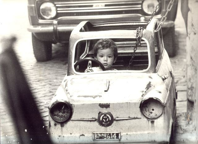 Jak widać na zdjęciu (wykonanym w latach 50.tych), już od dziecka byłem fanem motoryzacji. Co prawda mój pojazd (prezent od ojca chrzestnego, który pracował wtedy za granicą), zaparkowany zaraz przed naszym rodzinnym samochodem, wygląda tak, jakby przeszedł kilka wypadków, ale wynikało to z jego popularności. Wszyscy chłopcy z podwórka, nawet starsi ode mnie, chcieli się ze mną przyjaźnić, pewnie ze względu na 'furę'. Nie mieliśmy miejsca na zabawkę tych wymiarów w domu, stała na dworze (jak prawdziwe auto!), więc jaka była moja rozpacz, kiedy pewnego dnia 'niebo' (bo tak, od koloru, nazywałem samochodzik. Słowo honoru, gdy chciałem się pobawić mówiłem do Mamy: 'Idę do nieba') zginęło! Jednak, w tak małej miejscowości szybko znaleziono tych, co 'pożyczyli na wieczne nieoddanie', a gdy samochód znów znalazł się pod naszym domem Tata zdecydował na założenie szczególnego zabezpieczenia - grubego łańcucha (który widać na zdjęciu) z kłódką. Nie przeszkadzało mi to 'jeździć' w nieznane... podróże za jeden uśmiech. Nie pamiętam już, co stało się z 'niebem', kiedy wyrosłem. Wiem, że przypomniałem sobie o nim, gdy zdawałem prawo jazdy: samochodem marki Warszawa w takim samym blado - niebieskim kolorze. To były czasy...