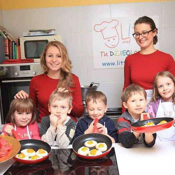 Mali Kucharze z gotowymi ciasteczkami: od lewej Emma (trzyma pomidorki), Jagódka (w ręku patelnia z jajkami), Antoś, Tomek i Staś (obaj chłopcy z patelniami), Marysia i Zosia (na talerzu ma pokrojone salami). Oraz panie z Little Chefa, które trochę pomogły: Ola (blondynka) i Gosia (brunetka, w okularach).
