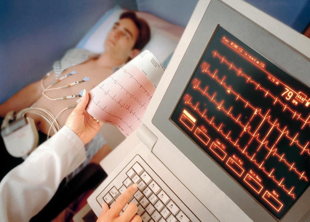 Zdjęcie przedstawia pacjenta podczas badania elektrokardiograficznego. Badanie to wykonywane jest w celu zdiagnozowania arytmii. Zmiany rytmu rejestrowane są jako przerwy w prawidłowym zapisie pracy serca