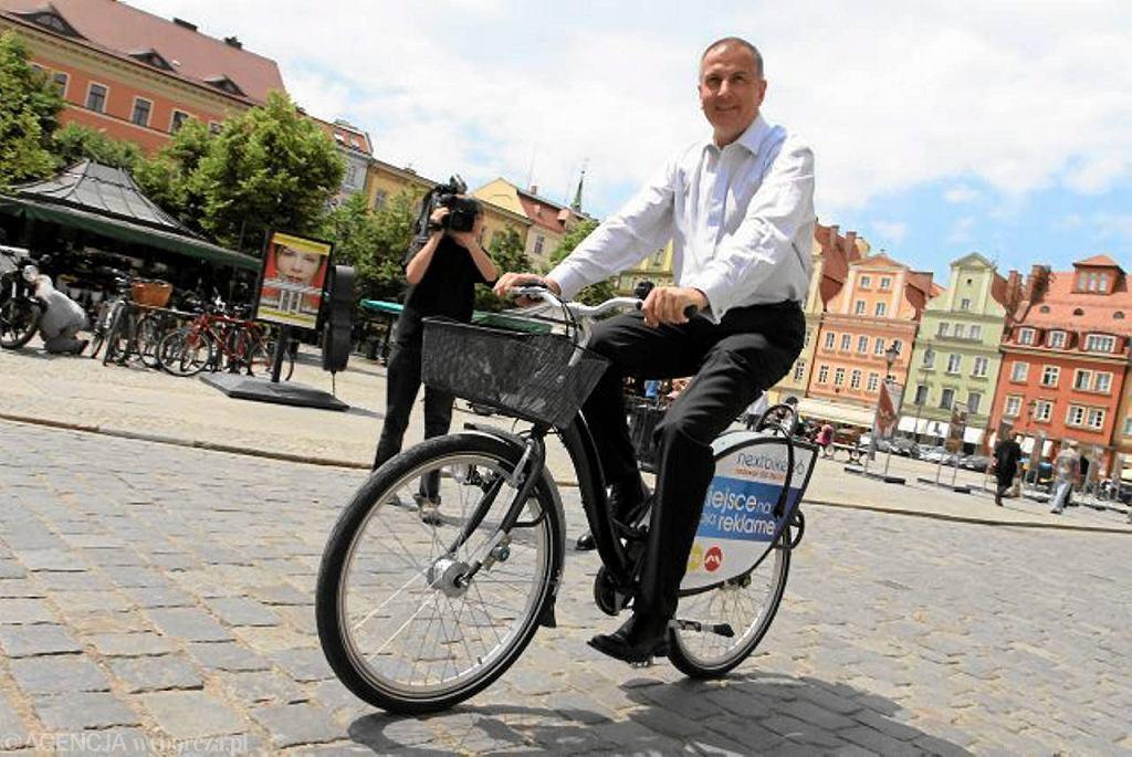 Rafał Dutkiewicz na wrocławskim rynku promuje wypożyczalnię rowerów miejskich