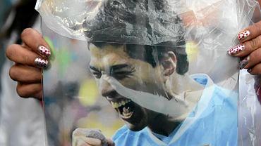 Kibic trzema plakat z Luisem Suareze,