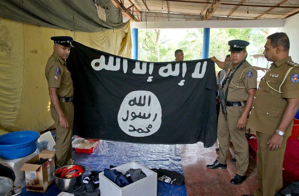 Lankijska policja prezentuje flagę dżihadystów znalezioną wraz z materiałami wybuchowymi w jednej z ich kryjówek. Napis głosi: 'Nie ma boga prócz Allaha, a Mahomet jest jego prorokiem'. Ampara, 28 kwietnia 2019 r.