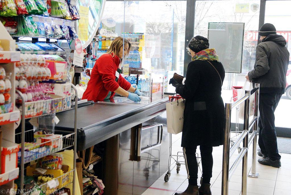 W sklepie PSS Społem 'Zgoda' w Płocku przy Tumskiej. Sprzedawców i klientów dzieli osłona z pleksi