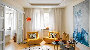 Wydaje się do mieszkania o każdej porze dnia zagląda słońce. Taki efekt daje jasna kolorystyka z akcentami ciepłych żółci i oranżów. Pokój dzienny właściciele urządzali sami. wstawili do niego niewiele mebli, za to o ciekawych, przyciągających uwagę kształtach.