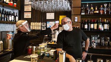 Właścicielka restauracji 1920 Tavern Jenna Aronowitz mierzy temperaturę barmana Shane'a Goode'a przed otwarciem, Brookhaven w Georgii, 27 kwietnia