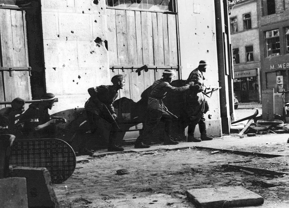 Grupa uzbrojonych powstańców z kompanii 'Koszta' przy narożniku kamienicy na ul. Sienkiewicza 11.