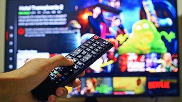 Pilot w dłoni, w tle telewizor. Zdjęcie ilustracyjne