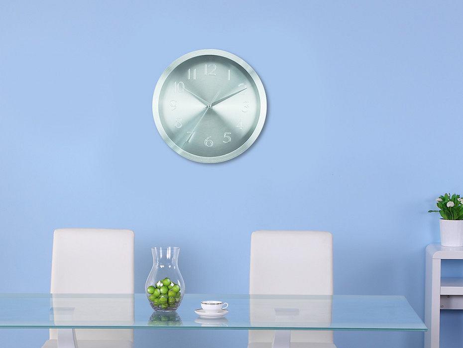 Srebrzysty zegar do kuchni na tle błękitnej ściany