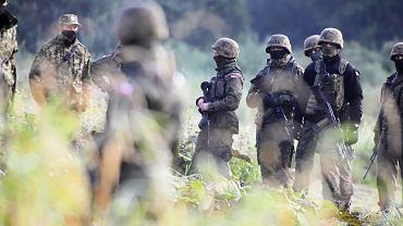 Straż graniczna, ludzie w wojskowych mundurach (pozbawionych oznaczeń identyfikujących formację) i policja od kilkunastu dni przetrzymują pod gołym niebem grupę migrantów. Nie przyjmują od nich wniosków o azyl, nie dopuszczają do nich pomocy, ich pełnomocników i dziennikarzy. Białorusini ni pozwalają im się cofnąć. Usnarz Górny, 22 sierpnia 2021