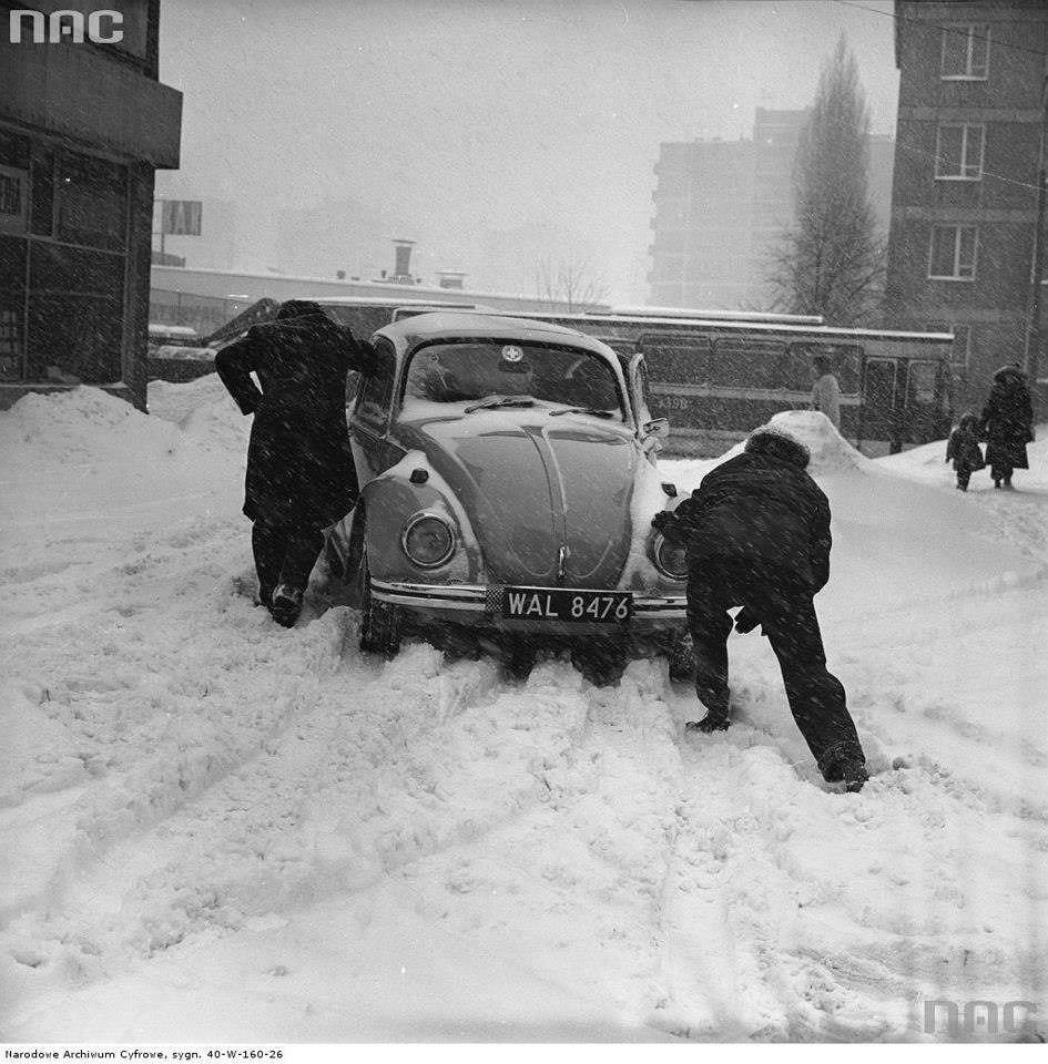 Mężczyźni pchający samochód volkswagen garbus w czasie