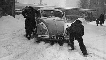 """Mężczyźni pchający samochód volkswagen garbus w czasie """"zimy stulecia"""", 1979 r."""