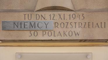 Tablica na budynku przy Nowym Świecie 49 w miejscu rozstrzelania 30 Polaków 12 listopada 1943 r. z naklejoną plakietką z wyrazem 'Niemcy'