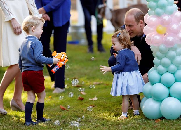 Britain's Prince William and Princess Charlotte look on as Prince George plays with a bubble gun at a children's party at Government House in Victoria, British Columbia, Canada, September 29, 2016. REUTERS/Chris Wattie