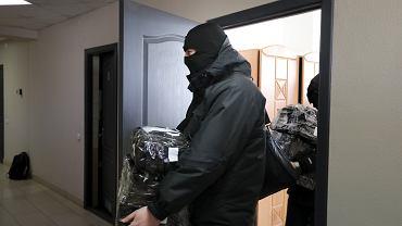 Władze Białorusi dokonały nalotu na domy i biura dziennikarzy oraz działaczy na rzecz praw człowieka. To najnowszy krok mający na celu stłumienie fali demonstracji przeciwko autorytarnemu prezydentowi Aleksandrowi Łukaszence. Na zdjęciu: policjanci wynoszą dokumenty i komputery zarekwirowane w siedzibie  Białoruskiego Zrzeszenia Dziennikarzy, Mińsk, 16 lutego 2021 r.