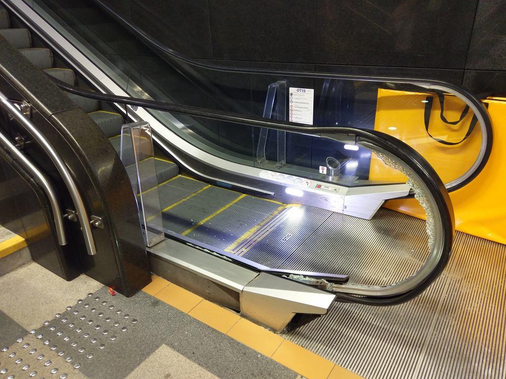 Rozbita tafla szkła przy schodach ruchomych