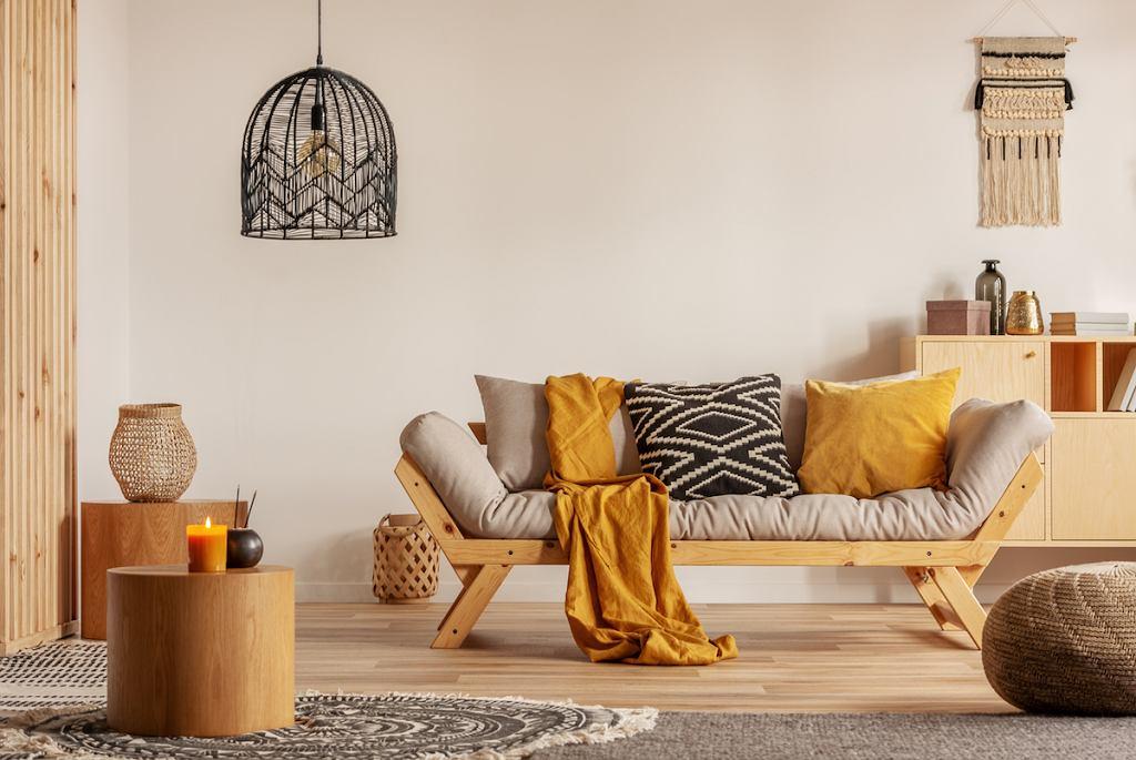 Wnętrze z dużą ilością drewna, w którym sofę udekorowano jednolitymi i wzorzystymi poduszkami.