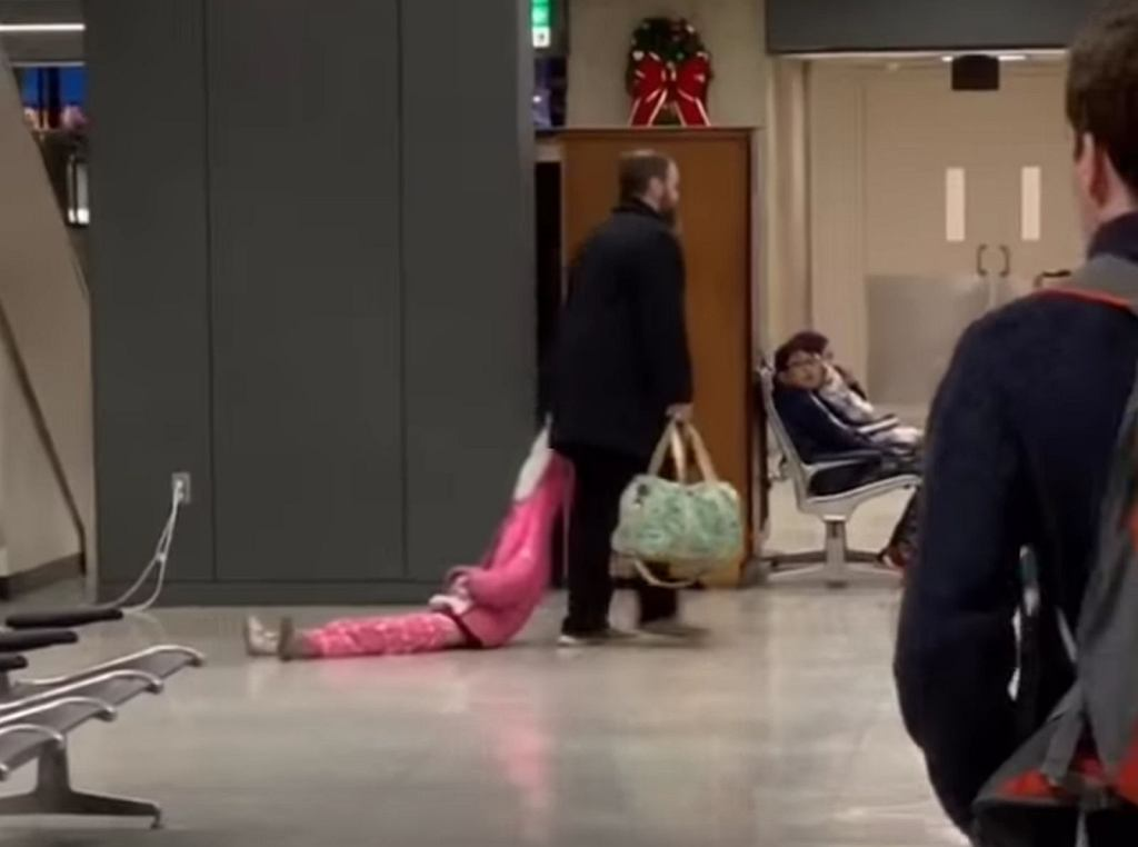 Ojciec ciągnął córkę po podłodze lotniska, trzymając ją za kaptur kurtki