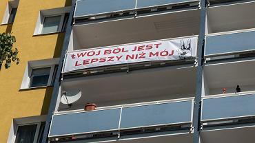 Baner na balkonie ze słowami piosenki Kazika 'Twój ból jest lepszy niż mój'