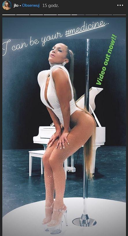 Jennifer Lopez w ultra wysokich szpilkach i  skąpym kostiumie opiera się o rurę