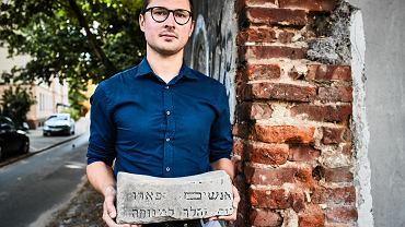 Dr Adam Sitarek, historyk łódzkiego getta, trzyma fragment macewy znalezionej przy ul. Żeromskiego. Stoi na ul. Rybnej, obok muru nieistniejącego cmentarza żydowskiego.