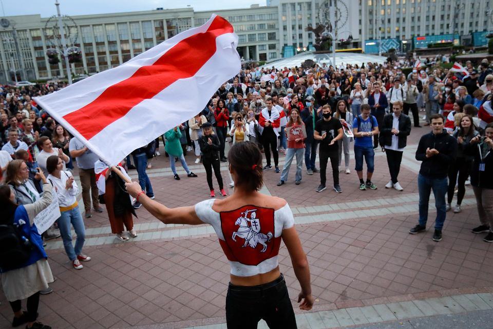 Młody Białorusin podczas manifestacji na placu Niepodległości w Mińsku wymachuje historyczną flagą kraju. Na plecach ma namalowaną Pogoń - godło Wielkiego Księstwa Litewskiego i Białorusi