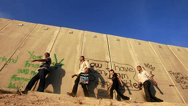 Palestyńczycy idą wzdłuż izraelskiego muru w pobliżu check-pointu Qalandia, przez który mogą się dostać do Jerozolimy. 9 kwietnia Izrael czekają wybory parlamentarne, startują w nich także partie arabskie reprezentujące 20 proc. społeczeństwa