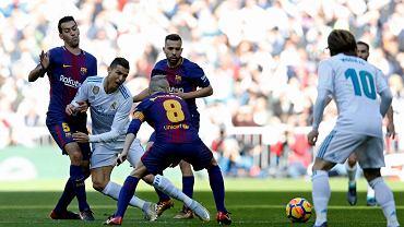 Real Madrid's Cristiano Ronaldo falls between Barcelona's Sergio Busquets, left, and Barcelona's Andres Iniesta during the Spanish La Liga soccer match between Real Madrid and Barcelona