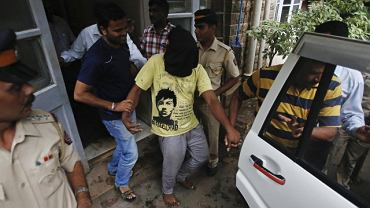 Indyjska policja prowadzi jednego z oskarżonych za gwałt na fotoreporterce.