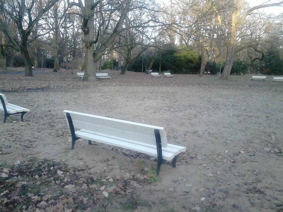 Białe ławki widać z daleka w całym parku