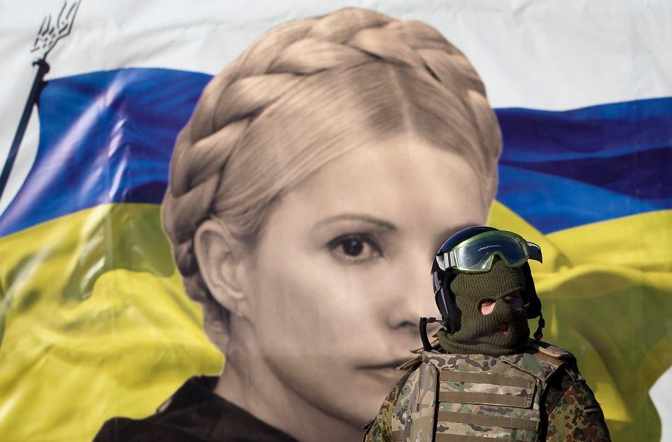 Umundurowany protestujący na tle flagi Ukrainy z portretem Julii Tymoszenko