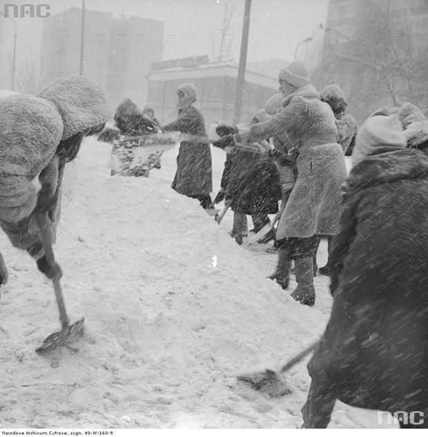 Mieszkańcy Warszawy odśnieżający chodnik w czasie
