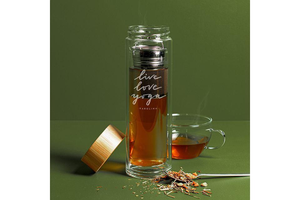 Szklana butelka z zaparzaczem do herbaty oraz elementami ze stali nierdzewnej i bambusową zakrętką.