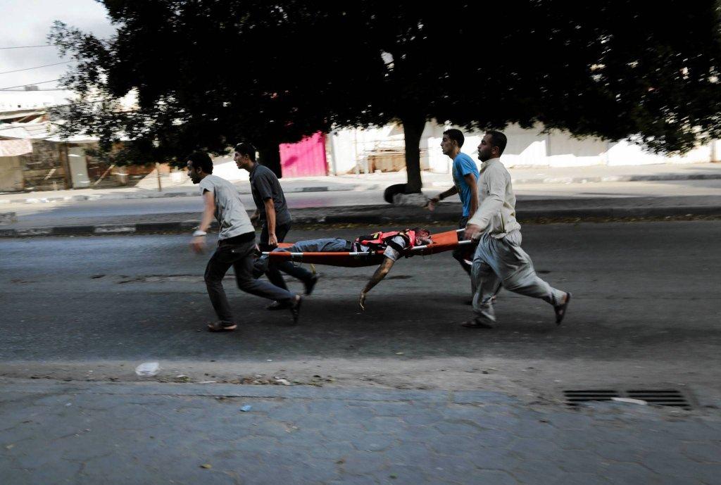Ranny niesiony na noszach do karetki w mieście Gaza