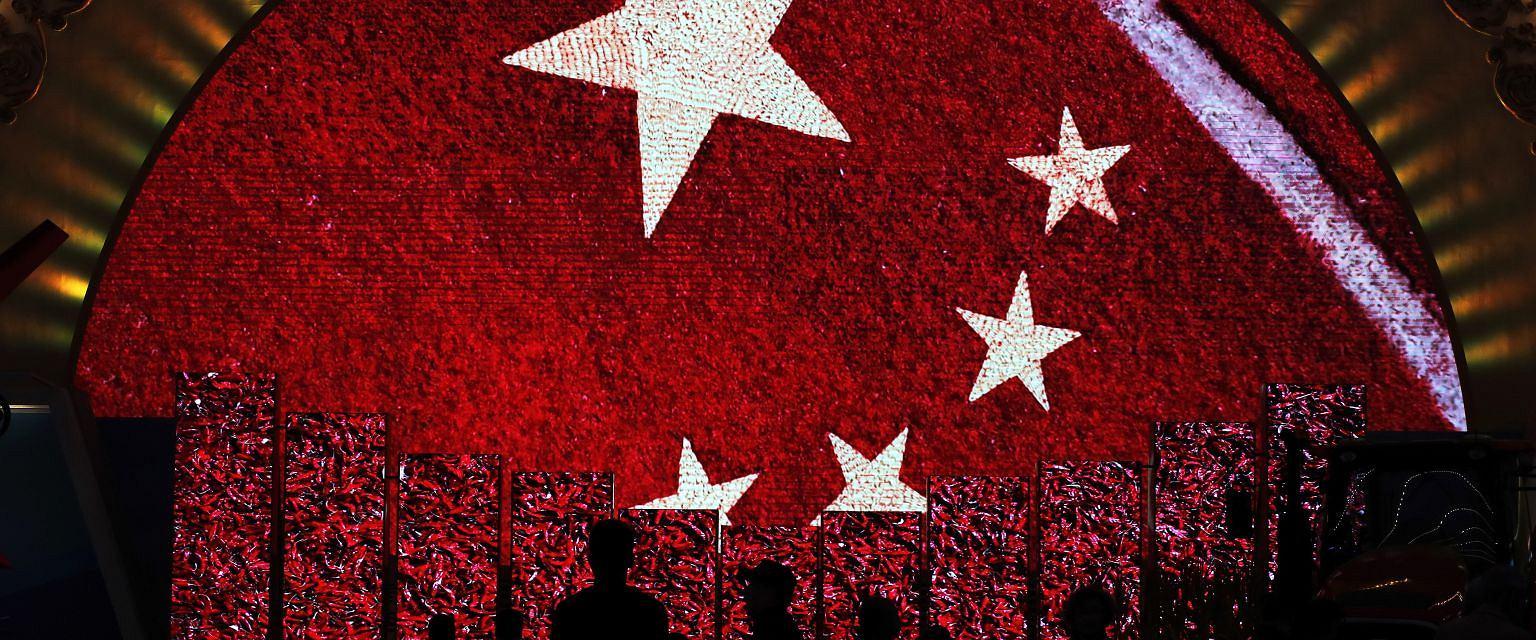 Chińska flaga na wystawie dokumentującej osiągnięcia Chin po pięciu latach rządów Xi Jinpinga (fot. Andy Wong/Associated Press)