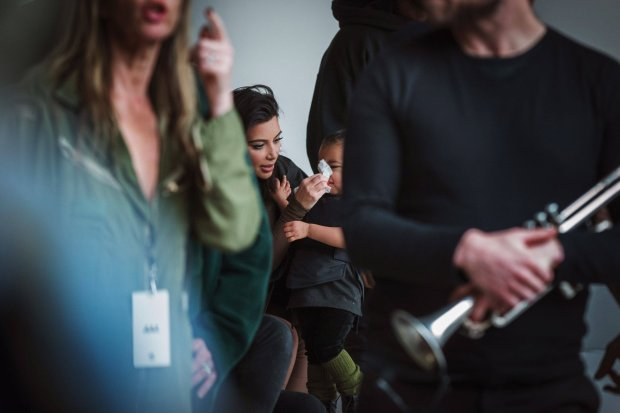 Kim Kardashian cleans the nose of her daughter, North, before a presentation of Kanye Wests Fall/Winter 2015 partnership with Adidas at New York Fashion Week February 12, 2015. REUTERS/Lucas Jackson (UNITED STATES - Tags: FASHION SOCIETY ENTERTAINMENT TPX IMAGES OF THE DAY)