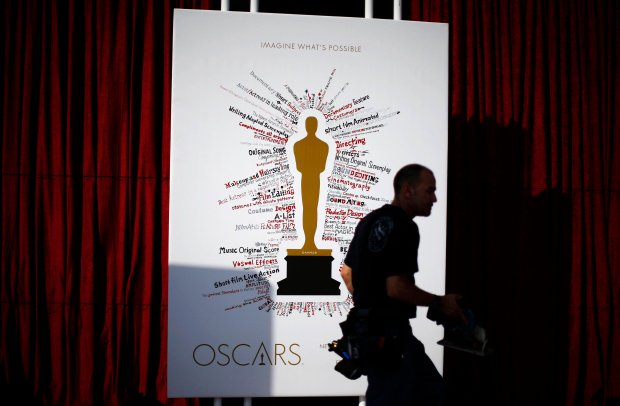 A worker walks past an Oscar poster outside the Dolby Theater during preparations ahead of the 87th Academy Awards in Hollywood, California February 20, 2015. The Oscars will be presented at the Dolby Theater February 22, 2015. REUTERS/Lucy Nicholson (UNITED STATES - Tags: ENTERTAINMENT)