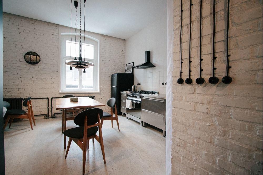 W kuchni postawiono na stalowe szafki. Stylowo prezentuje się czarna lodówka w duchu retro