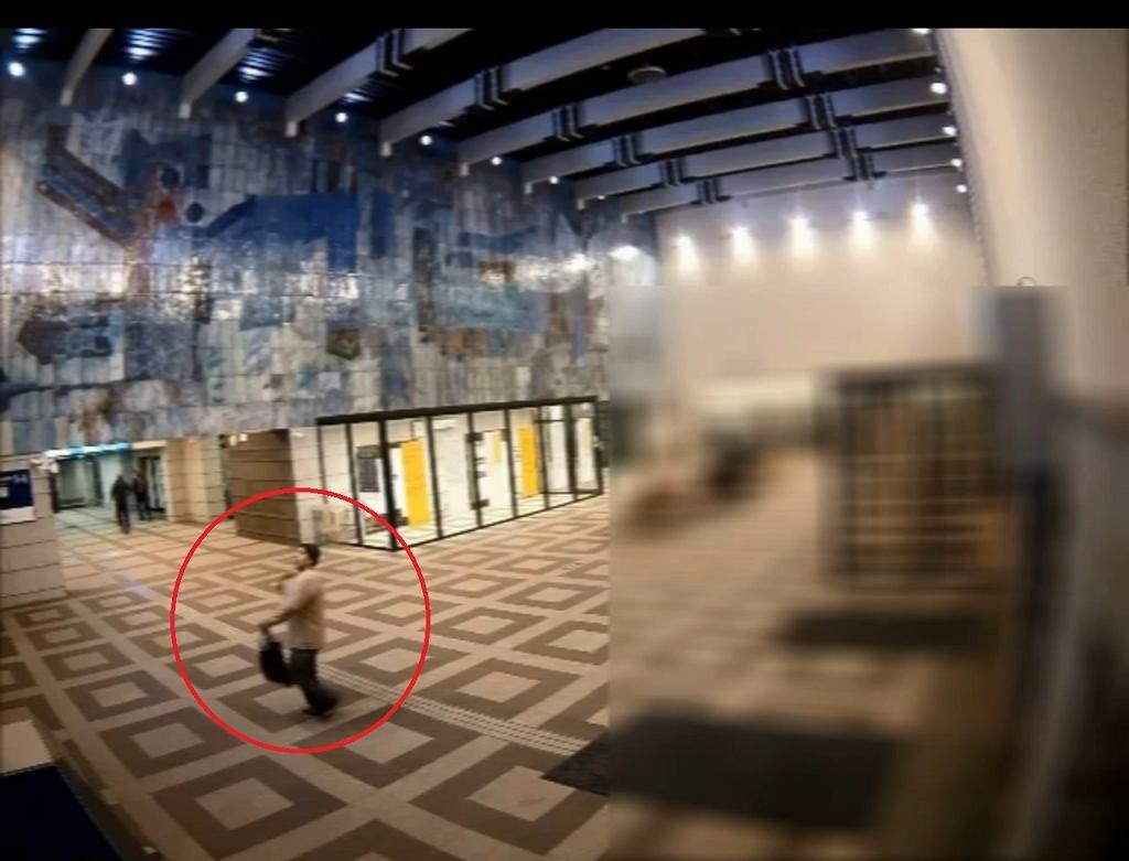 Ujęcie z kamery na dworcu. Mężczyzna ciska siekierą, którą wyjął spod ubrania.