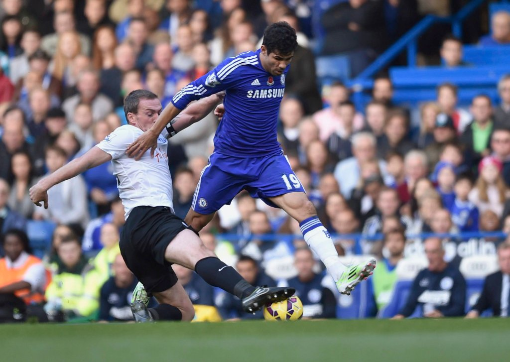 Chelseas Diego Costa challenges Queens Park Rangers Richard Dunne during their English Premier League soccer match at Stamford Bridge in London