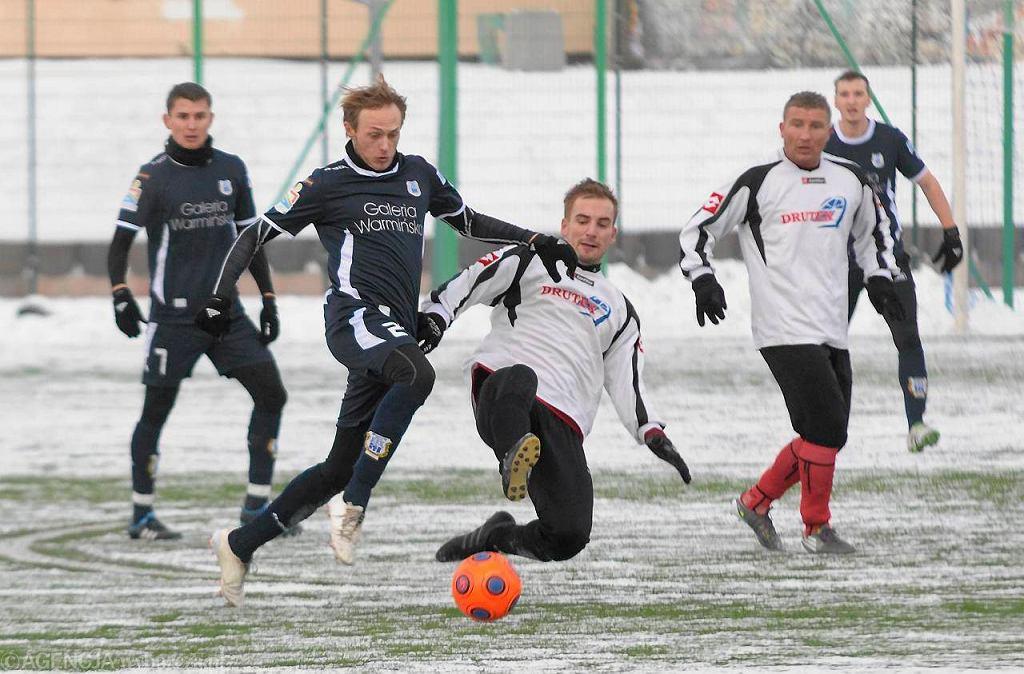 Zimowy trening piłkarzy Stomilu Olsztyn. O piłkę walczy Grzegorz Lech