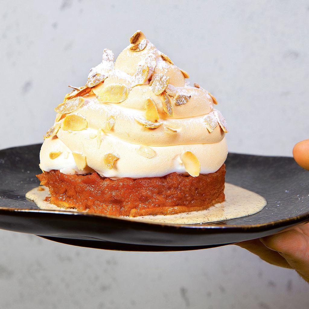 Szarlotka. Flagowy deser restauracji ANóż Widelec przygotowany na wzór Baked Alaska. Podstawą są szare renety albo odmiana boskoop. Wewnątrz, na spodzie zkruchego ciasta, ukryte są lody waniliowe własnej roboty, wokół prażone 7-8 godzin jabłka. Wszystko przykrywa beza włoska obsypana migdałami. Deser zostaje zamrożony, atuż przed podaniem zapieka się go wpiecu 12-13 minut. Dzięki temu lody znajdujące się wewnątrz nie rozpuszczają się, azzewnątrz całe ciasto jest gorące.