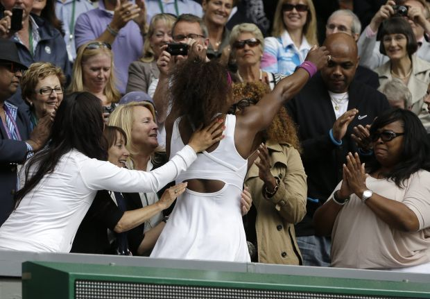 Serena Williams of the United States, center left, hugs her mother Oracene Price, center right, after defeating Agnieszka Radwanska of Poland to win the women's final match at the All England Lawn Tennis Championships at Wimbledon, England, Saturday, July 7, 2012. (AP Photo/Alastair Grant)