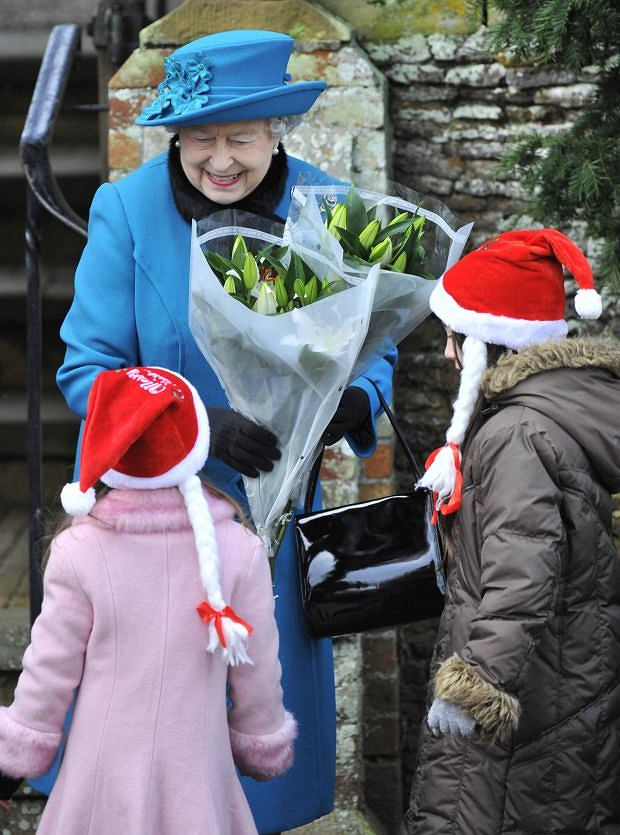 Britain's Queen Elizabeth receives flowers outside of St. Mary's church after attending the annual Christmas service on the Royal Estate at Sandringham in Norfolk, eastern England December 25, 2012. REUTERS/Toby Melville (BRITAIN - Tags: ROYALS SOCIETY)