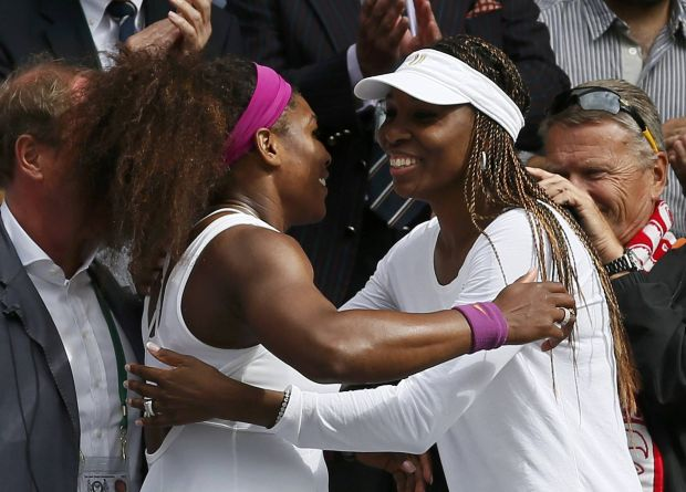 Serena Williams of the U.S. (L) hugs her sister Venus after defeating Agnieszka Radwanska of Poland in their women's final tennis match at the Wimbledon tennis championships in London July 7, 2012.      REUTERS/Stefan Wermuth (BRITAIN  - Tags: SPORT TENNIS)
