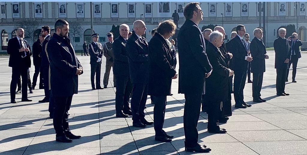 Zbliżenie na zdjęcie kilkunastu polityków PiS, którzy w piątek rano zgromadzili się na placu Piłsudskiego przed pomnikiem ofiar katastrofy smoleńskiej