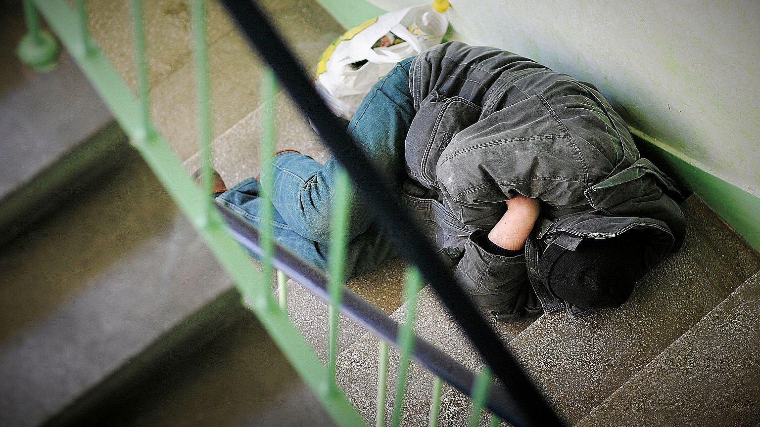 Bezdomny śpiący na klatce schodowej