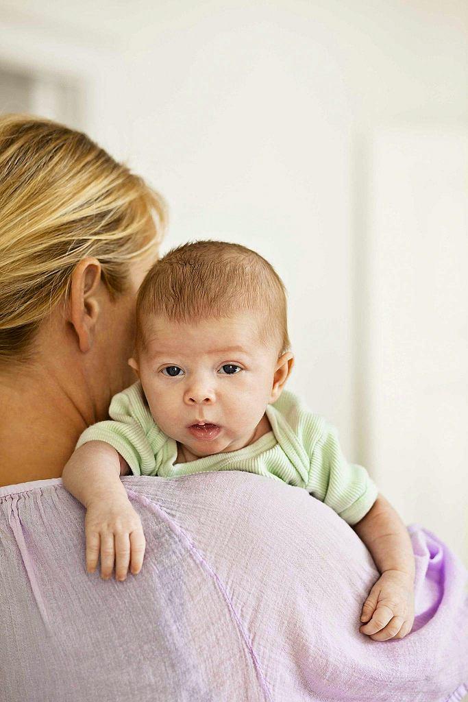 W pozbyciu się połkniętego w czasie karmienia powietrza pomoże dziecku noszenie przez kilka minut w pozycji zbliżonej do pionu.